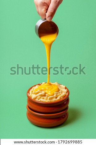 Cooking mac and cheese with melted cheddar cheese dripping over boiled macaroni, isolated on a green background. Pouring cheese on pasta. Hot food.