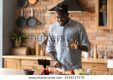 Cooking master class. Confident black man vlogger shoot tutorial teach audience to make healthy food. Young african guy capable cook broadcast live preparing national cuisine dish on domestic kitchen ストックフォト ©