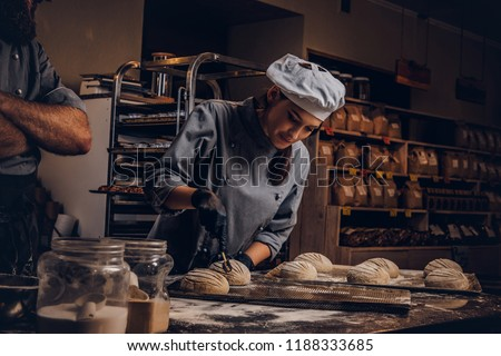 Cooking master class in bakery. Chef with his assistant showing ready samples of baking test in kitchen.