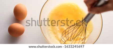 Cooking, meal and diet concept - Making of mixing eggs in bowl on marble table as homemade food flat lay, top view food brand photography flatlay and recipe for cooking blog, menu or cookbook design