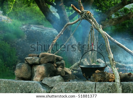 Cooking outdoors in a cauldron on a campfire