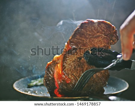 Cooking pan seared ribeye steak in nonstick teflon coating pan with kitchen tongs and fork on dark background with smoke and fog. People enjoy home cooking lifestyle concept /close up, selective focus