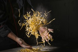 Cooking pasta spaghetti dough with flour on dark black background with space area. Food banner, big size resolution.