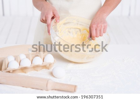 Cooking pastry. Close-up of woman mixing dough in a mixing bowl