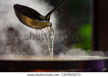 Cooking person in the restaurant is cooking while using the dipper in a large pot. And the water is boiling, there is smoke, hot spit.