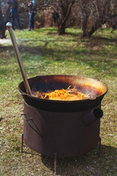 Cooking pilaf in a large cauldron outside on a picnic. Cooking Uzbek holiday pilaf. Carrots and meat in a cauldron with rice on a live fire in a huge cauldron for pilaf