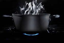 Cooking pot on stove fire with food inside in a dark kitchen and a black background with steam coming out of the cooking pot, low key light, and dark food. cooking at home or culinary school concept.