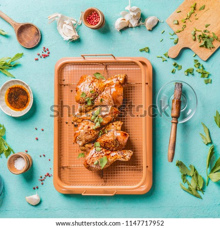 Cooking preparation of raw chicken drumsticks. Raw marinated Chicken legs on grill grid with ingredients,  herbs, spices , sauce and cooking spoon on light blue kitchen table background, top view