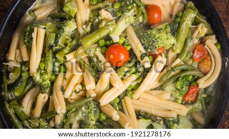 Cooking primavera pasta in a pan - vegan american and italian primavera pasta dish with broccoli, beans, asparagus, peas and tomatoes in a pan on a wooden table, top view Foto stock ©