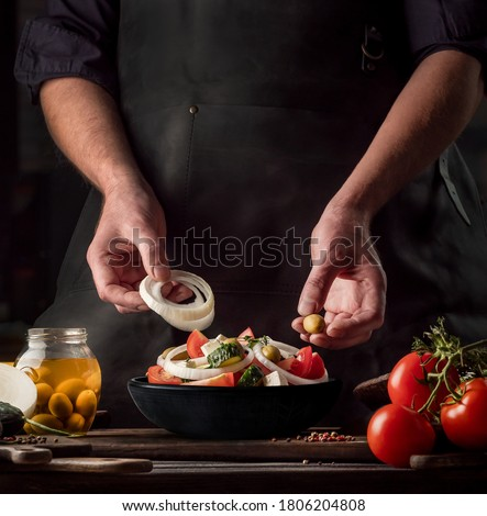 Cooking process of Greek Salad for a restaurant menu. Food composition of a Mediterranean cuisine in rustic style. Chef put the onion and olives in a black bowl and mixed of all vegetables in a salad.