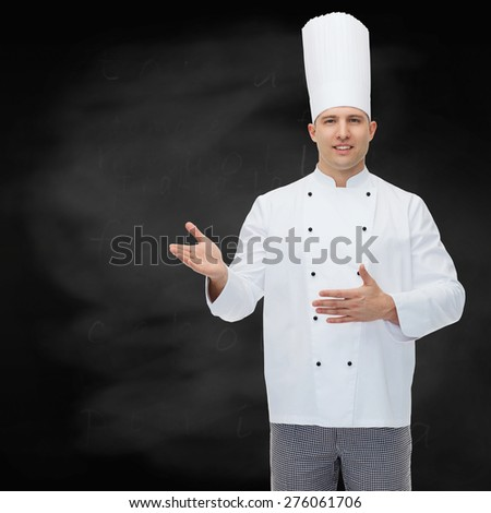 cooking, profession and people concept - happy male chef cook inviting over black chalk board background