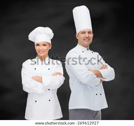 cooking, profession and people concept - happy male chef cook with crossed hands over black chalk board background