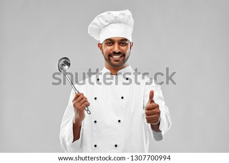cooking, profession and people concept - happy male indian chef in toque with ladle showing thumbs up over grey background