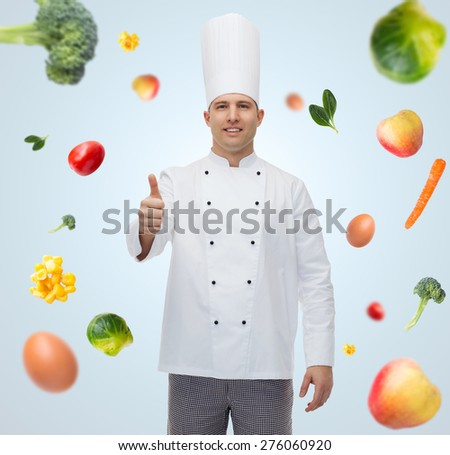 cooking, profession, gesture, vegetarian diet and people concept - happy male chef cook showing thumbs up over blue background with falling vegetables