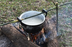 Cooking rice using pot in outdoor nature. Food Camping cooking over a fire using dry firewood and use stone as stove stand.