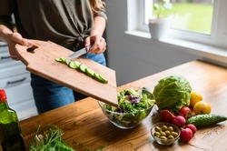Cooking salad at home. A woman throws cucumber from cutting board in salad, fresh vegetables and greens on the table near. Healthy food concept. Face is not visible