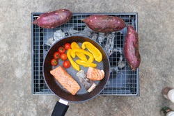 Cooking salmon fillet on pan with Japanese sweet potatoes grilling on charcoal oven. Outdoor cooking with healthy meal.
