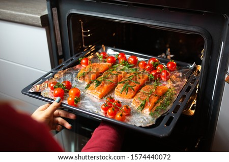 Cooking salmon in the oven. Housewife is preparing dinner. The chef is cooking red fish. Cooking fish in the oven. Girl takes out baked salmon with cherry rinds from the oven.World food day