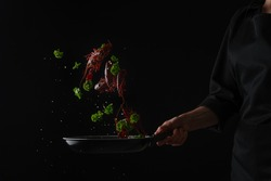 Cooking seafood, frying crayfish in a pan with greens, freezing in motion, cooking for the restaurant menu, hotel business, gastronomy