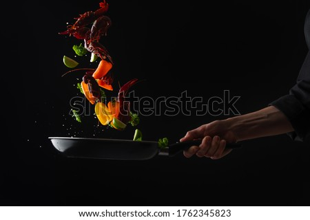 Cooking seafood, frying in a pan with vegetables, veggie healthy food, on a black background, menu and restaurant business Foto stock ©