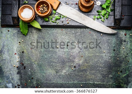 Cooking set with Kitchen knife with table spices, salt and pepper mills on rustic background , top view, place for text