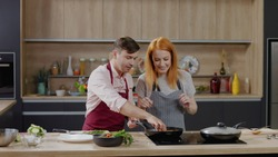 Cooking show hosts chefs, male and female, cooking meat. Morning TV cooking programme