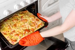 Cooking simple delicious food at home.A woman cooks a delicious square pizza with pepperoni, tomatoes and cheese in the oven.He takes his hands out to check that they are ready.Cooking process