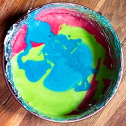 cooking sweet sponge cake at home - top view of multicoloured mix of raw dough in springform pan on old wooden table at home kitchen