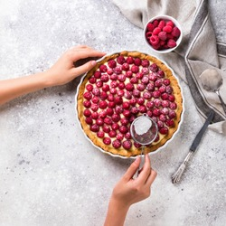 Cooking the cake. Baking with raspberries. Preparation for the tart. Hands of the young woman put summer berry.