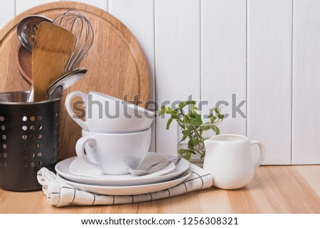 Cooking utensils and tableware stnding on the wooden table. Moden kitchen dishware and accessories. #1256308321