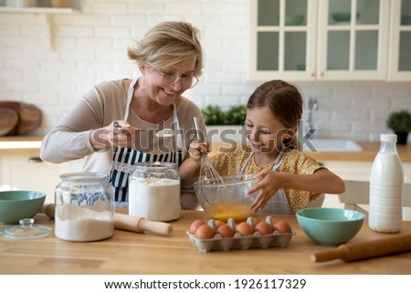 Cooking with soul. Happy little girl in apron help senior grandma at kitchen mix dough for cookies pancakes. Smiling older granny teach small grandkid to bake homemade cake pastry share family recipe Stock photo ©