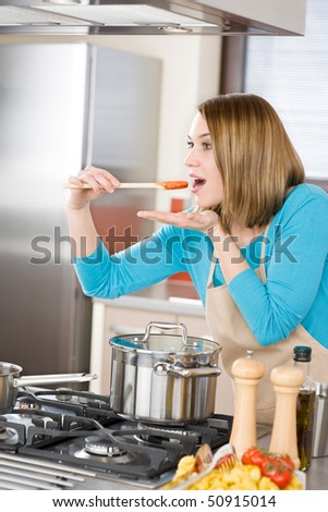 Cooking - Young woman tasting Italian tomato sauce in modern kitchen, with tomatoes and tortellini pasta