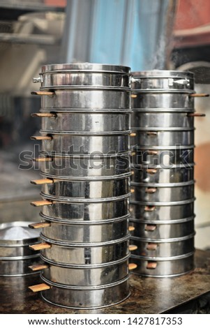 Cookware from a foodstand in the Jade Market consisting of multilevel stainless steel steamers or manti-kaskan for the steaming of manta dumplings -mainstay of Uyghur cuisine. Hotan-Xinjiang-China.
