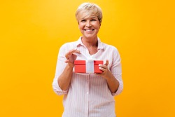 Cool adult lady smiles and holds gift box on orange background