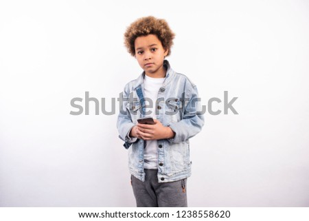 Cool african american boy talking on the phone, chatting and making selfie. Kids and gadgets. Modern children. New pics on white background. Shooting in November 2018.