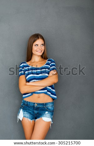 Cool and cute. Happy young woman keeping arms crossed and smiling while standing against grey background
