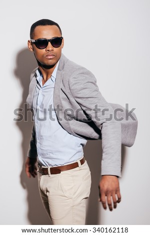 Cool and trendy. Confident young African man in sunglasses wearing jacket and looking over shoulder while standing against white background #340162118