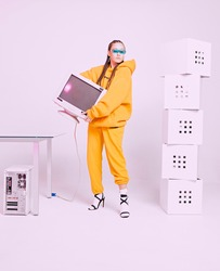 Cool asian female office worker with obsolete computer monitor and boxes. Colored Neon light