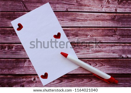 Cool background. Wood table. Romantic letter for lovers with red hearts and pen.
