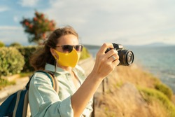 Cool beautiful happy girl woman traveler by the sea with a mask on her face, stylish outfit, with a camera in her hands