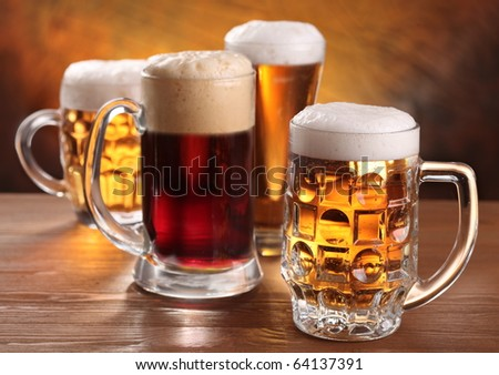 Cool beer mugs over wooden table.