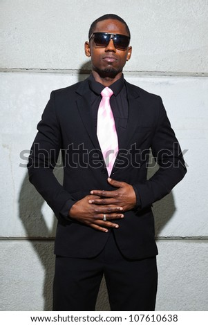 Cool black american man in dark suit wearing sunglasses. Fashion shot in urban setting.