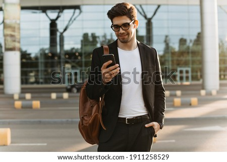 Cool brunette man in eyeglasses chats in phone. Happy guy in black suit holds brown backpack and smiles outside.