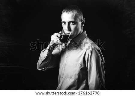Cool businessman standing on dark gradient background. Picture of a young casual man, over black background.