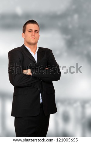 Cool businessman standing on light  background