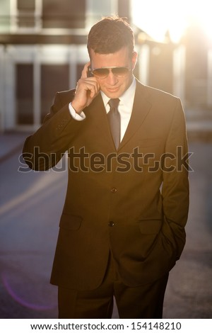 Cool businessman taking a call in front of an office building