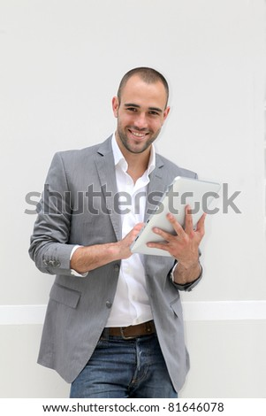 Cool businessman using electronic tablet on white background