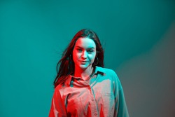 Cool confident young girl in colored neon studio light. Modern creative woman beauty portrait. Copy space for ad