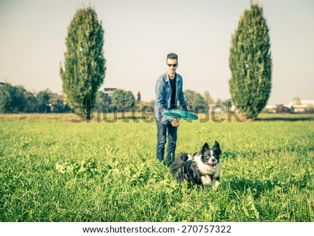 Cool dog and young man having fun with frisbee in a park - Australian shepherd dog running  and trying to catch a frisbee - Concepts of friendship,pets,togetherness.Focus on frisbee