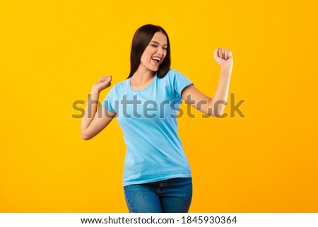 Cool Energy Concept. Excited joyful lady dancing and having fun isolated on yellow background. Optimistic female student celebrating win or victory, standing over orange studio wall, free space Foto stock ©